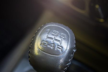 Close up view of a gear lever shift. Car interior.