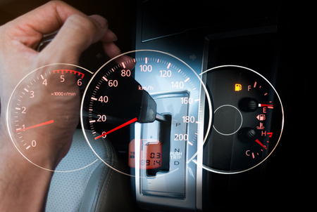Hand with Car gear stic with speedmeter car dashboard.