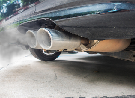 Incomplete combustion creates poisonous carbon monoxide form exhaust pipe of black car, air pollution concept.