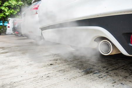 Incomplete combustion creates poisonous carbon monoxide from exhaust pipe of white car, air pollution concept.