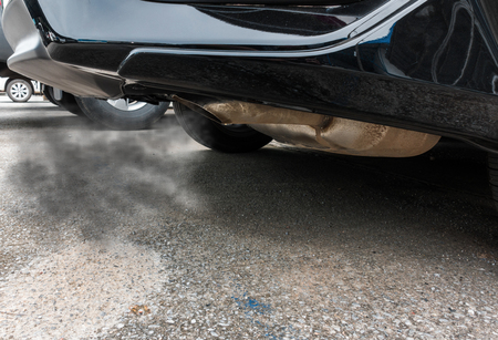 Combustion fumes coming out of black car exhaust pipe, air pollution concept. Stock Photo
