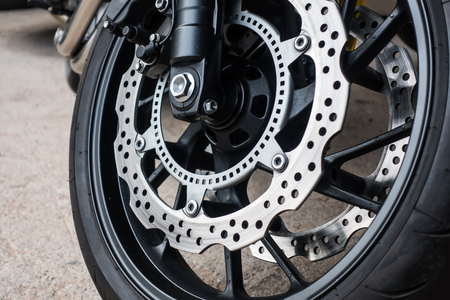 Closeup detail of racing motorcycle disk brake with ABS system and tire on road