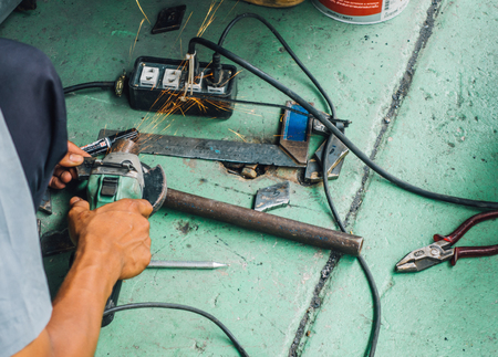 Careless worker use hand grinding without  safety gloves, outlet generating electricity sparks