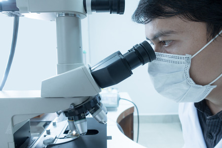 Male scientist doing microscope for chemistry test samples, examining. Laboratory equipment and science experiments. Stock Photo