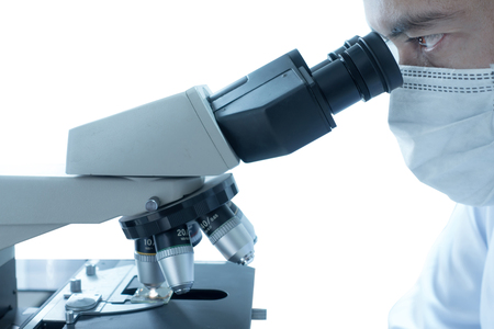 Male scientist doing microscope for chemistry test samples, examining. Stock Photo