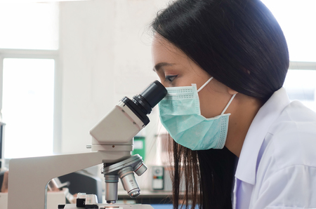 Female scientist doing microscope for chemistry test samples, examining. Stock Photo