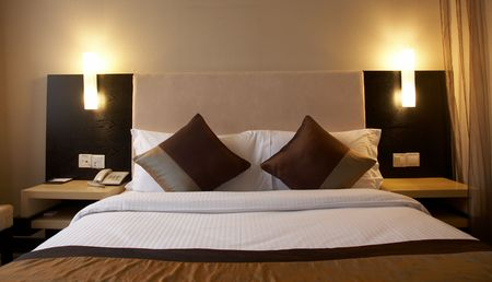 A   hotel bed with an ornate headboard and two glowing lamps on either side. photo