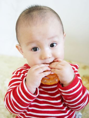 teether: Asian teething baby biting and playing his toy.