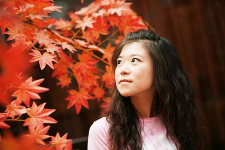 Sweet asian woman and red maple leaves in autumn day. photo
