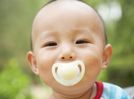 cheerful baby with a pacifier Stock Photo - 4811682