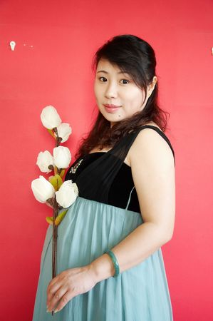 asian pregnant woman holding flowers against red background. photo