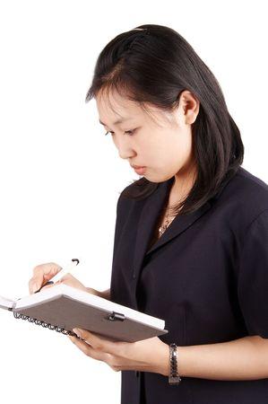 subordinated: asian secretary writhing something on notebook. Stock Photo