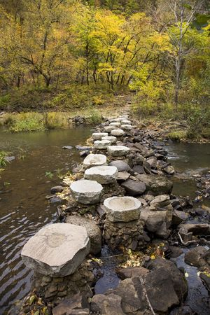 stepping stones  across stream to autumn forest photo