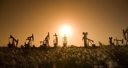 exploration: Silhouette of oil pump with sunset  Stock Photo