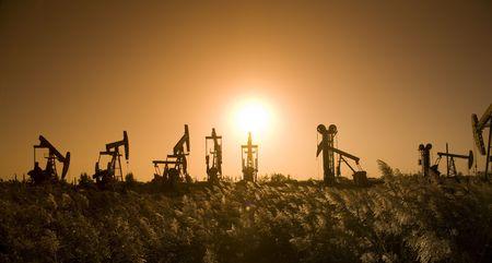 broca: Silueta de la bomba de aceite con la puesta del sol