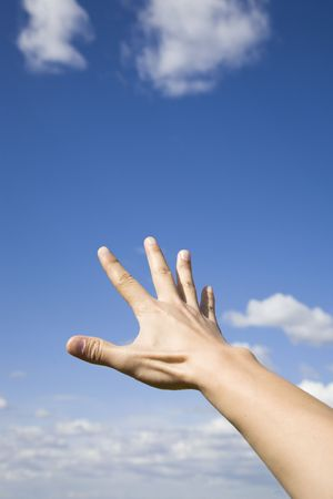Man's hand reaching up to the blue sky Stock Photo - 5887980