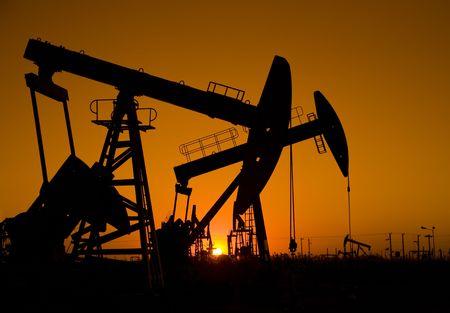 torres petroleras: Silueta de aceite se arregla con la puesta de sol  Foto de archivo