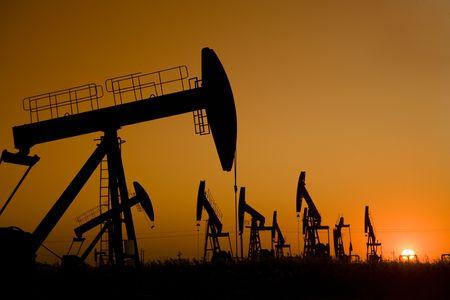 puits de petrole: Silhouette de puits de p�trole avec un coucher de soleil