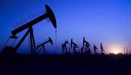 oil field: Silhouette of oil well with sunset Stock Photo