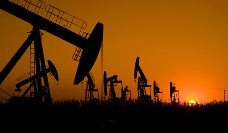 Silhouette of oil well with sunrise photo