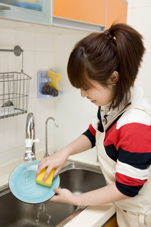 woman washing dishes in her kitchen photo
