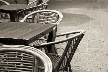 Sidewalk cafe with wicker chairs and table  photo