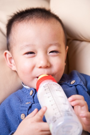 Baby boy with bottle of milk photo