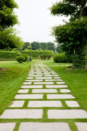 Stone paved path through the park lawn Stock Photo
