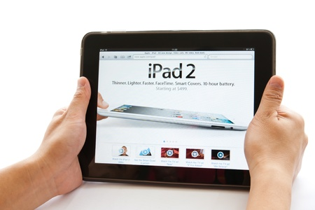 Beijing, China - June 25, 2011: Man's hands holding an Apple ipad displaying Apple Ipad2 web brower. The iPad was produced by Apple Inc. Stock Photo - 9774346