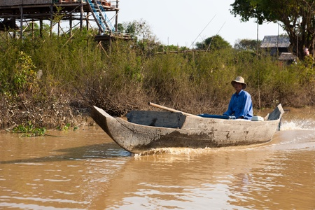 Cambodian man sitting in his boat on the river system of Tonle Sap Lake
