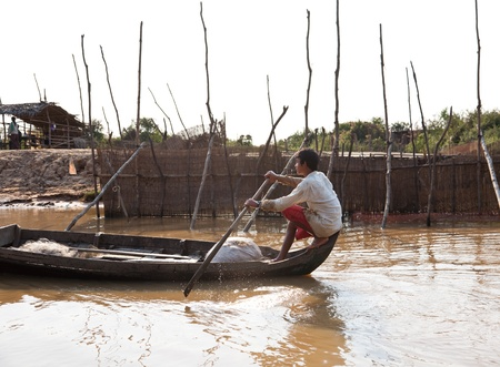 sap: Cambodian man paddling boat on the river system of Tonle Sap Lake  Editorial