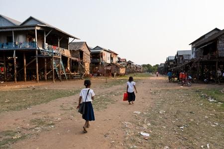 gente pobre: Kom Pong Plyuk, Siem Reap, Camboya - 03 de febrero de 2011: Dos estudiantes con uniformes escolares est�n caminando por el camino de tierra a trav�s de la aldea.