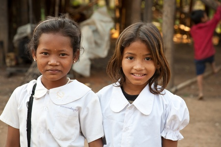 poor children: Kom Pong Pluke, Siem Reap, Cambodia - February 3, 2011:The portrait of two local smiling girl students wearing school uniforms.