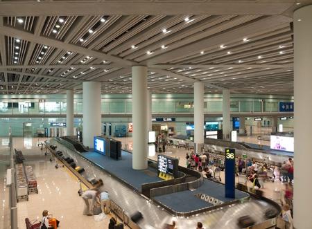 Los pasajeros que están tomando los paquetes en el área de equipaje de transporte, aeropuerto internacional de Beijing de capital Foto de archivo - 10591593