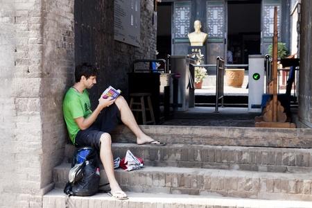 Un turista sentado en las escaleras de un edificio antiguo y la lectura de libros, Pingyao, provincia de Shanxi, China.