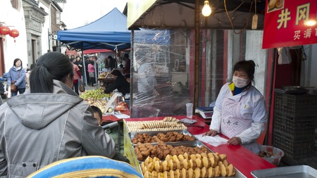 small town life: Suzhou, China - A street vendor is selling pastries and puddings. Some people are shopping at street market stall, Shan Tong Street, Suzhou.