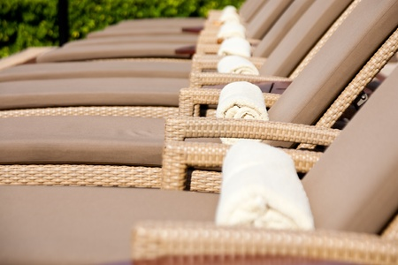 lobby: Empty lounge chairs by the poolside Stock Photo