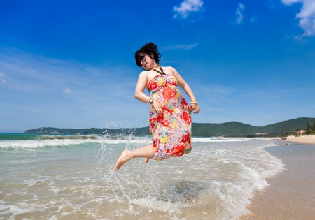 Happy woman jumping at beach photo