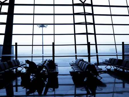 A traveller waiting for his plane at departure area. Beijing International Airport, China