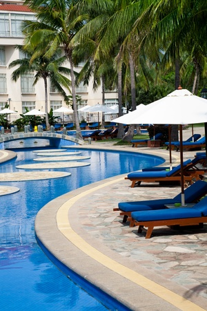 Resort poolside with recliners and sunshades. Golden Palm Resort of Sanya, Hainan Island, China