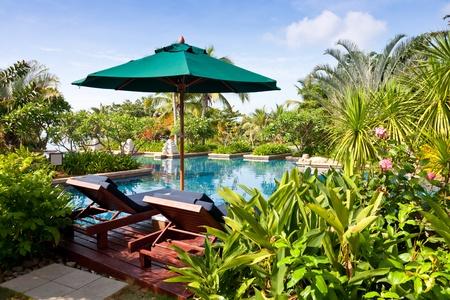 and sanya: parasol and deck chairs at poolside, Sheraton Sanya Resort, Hainan Island, China Editorial