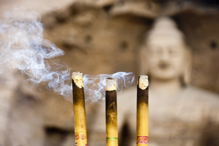 Three burning incense in front of a huge buddha statue. The focus is on the incense Stock Photo - 11238748