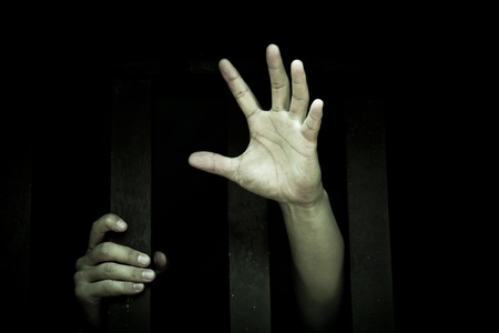 trapped: Human hand stretch out  from prison bars
