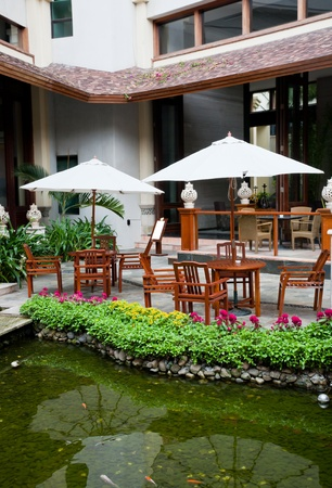 outdoor cafe: Garden patio with armchairs and umbrellas by the waterside, Eadry Resort Sanya, Hainan Island, China  Editorial