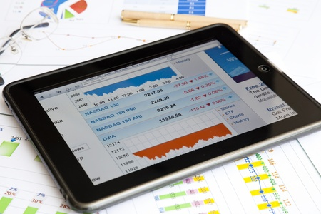 An ipad placed on paper financial reports with pen and glasses. The digital tablet with multi touch screen which showing nasdaq.com browser. The iPad was produced by Apple Inc. Editorial