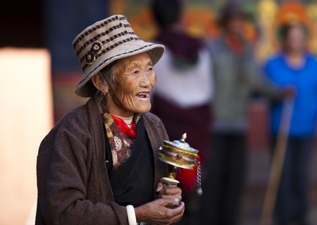Lhasa, Tibet, China - October 05, 2011: a senior female Tibetan prayer holding a prayer wheel at monastery.