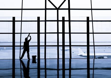 세탁기: 여자는 베이징 국제 공항에 창을 청소합니다. 에디토리얼