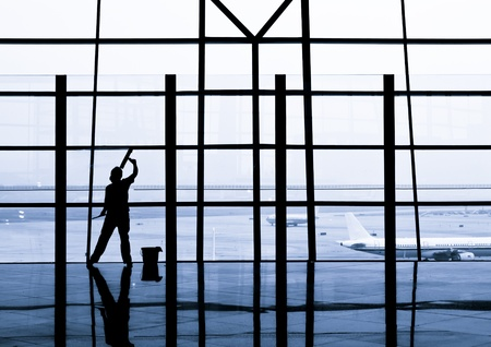 cleaning floor: A woman is cleaning windows at the Beijing International Airport.