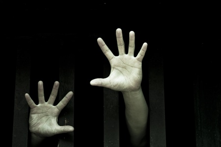Prisoner hands stretch out from prison bars 免版税图像 - 11433342