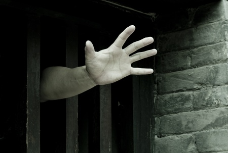 Prisoner hands stretch out from prison bars
